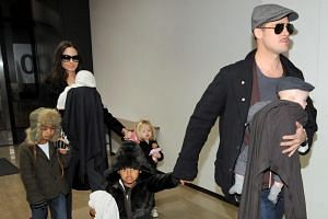 A file picture dated January 2009 shows Brad Pitt with his son Knox (in arms), daughter Zahara (left) as his partner, Angelina Jolie holds their daughter Vivienne and son Maddox and daughter Shiloh upon their arrival at Tokyo's Narita International A