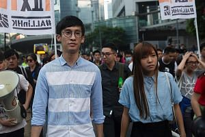 Mr Leung and Ms Yau protesting in Hong Kong on Sunday. They had refused to pledge allegiance to the city as part of China while being sworn into office last month. The National People's Congress, in its interpretation of the Basic Law, said their act