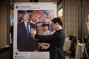 A woman poses for a photo with a cut-out of Donald Trump at an election event organised by the US embassy, at a hotel in Seoul on Nov 9, 2016.