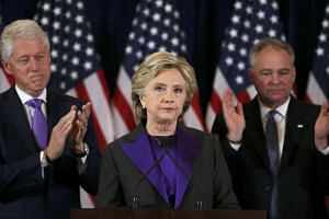 Hillary Clinton, accompanied by her husband former U.S. President Bill Clinton (L) and running mate Senator Tim Kaine, addresses her staff and supporters about the results of the US election at a hotel in New York, on Nov 9, 2016.
