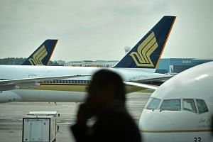 Singapore Airlines (SIA) planes parked on the tarmac at Changi Airport Terminal 3.