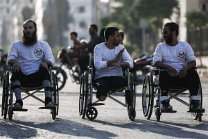 Disabled Syrian men, who sustained injuries in shelling and bombardment, prepare to compete in a makeshift wheelchair race in the rebel-held town of Douma, east of the capital Damascus, on Sept 8, 2016.