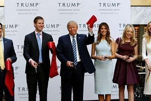Mr Donald Trump, flanked by his wife Melania and children - Donald Trump Jr., Eric, Tiffany and Ivanka - attend an official ribbon cutting ceremony at the new Trump International Hotel in Washington on Oct 26, 2016.