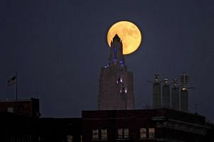 """The """"supermoon"""" rises over the Power and Light building in downtown Kansas City, Missouri, on Nov 13, 2016."""