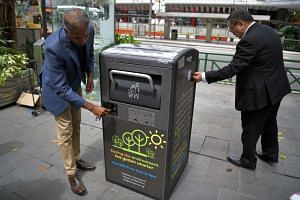 Jason Kumar, co-founder of Terra Sol (left) explaining the capabilites of the solar-powered smart compacting BigBelly bins as Mr Steven Goh, exectuive director of Orchard Road Business Association (ORBA) (right) looks at the bin.