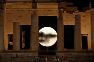 A rising supermoon is seen through the Propylaea, the ancient Acropolis hill gateway in Athens, on Nov 14, 2016.