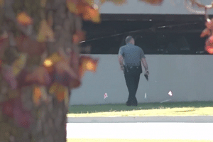 A police officer checks a parking lot in a screenshot from footage posted to YouTube.
