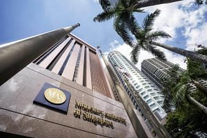 The Singapore national flag flies next to a Monetary Authority of Singapore (MAS) sign outside the central bank's headquarters in Singapore.