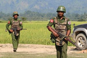 Armed Myanmar army soldiers patrol a village in Rakhine's Maungdaw.