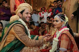 Brahmani (right), daughter of Gali Janardhan Reddy, sits with her groom, Rajeev Reddy during their wedding at the Bangalore Palace Grounds in Bangalore.