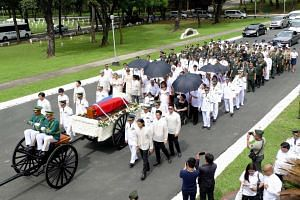 Members of the late dictator Ferdinand Marcos led by former first lady Imelda Marcos (in black) follow the hearse during the burial at the heroes' cemetery in Manila on Nov 18, 2016.