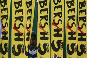 A protester is seen behind banners during the Bersih 5.0 rally in Kuala Lumpur, Malaysia on Nov 19, 2016.