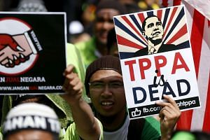 Protesters wave placards at a rally against the Trans Pacific Partnership (TPP)  free trade pact in Kuala Lumpur, Malaysia, Jan 23, 2016.