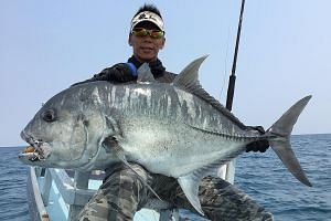 """Mr Ivan Goh, chief guide of Deep Sea Fishing, with a giant trevally caught last year in East Kalimantan, Indonesia. He said the company has stopped making trips to Indonesian waters where the anglers were arrested as a """"precaution""""."""