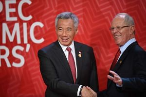 Singapore's Prime Minister Lee Hsien Loong shakes hands with Peru's President Pedro Pablo Kuczynski as he arrives at the Lima Convention Centre for the Apec Leaders' Retreat.