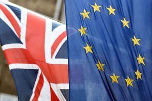 A British Union flag flies next to a European Union (EU) flag in London.