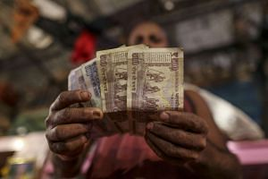 A vendor displays Indian five hundred, one hundred and fifty rupee banknotes in Mumbai, India on Nov 19, 2016.