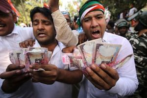 Indian Youth Congress activists show replicas of old Indian Rupee notes during a protest against the Rupee note change in New Delhi on Nov 18, 2016.