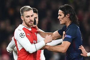 Paris Saint-Germain's Uruguayan forward Edinson Cavani (right) scuffles with Arsenal's Welsh midfielder Aaron Ramsey (left) after Arsenal were awarded a penalty.