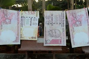 A couple on their morning walk are seen through a gap of replica prints of the demonetised 500 and 1000 rupee notes as part of a street art exhibition in Mumbai, on Nov 20, 2016.