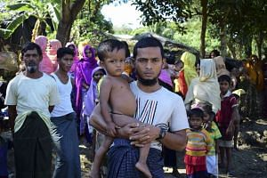 Rohingya refugee Mohammad Ayaz stands with his son Mohammad Osman, the two survivors of his family, at an unregistered refugee camp at Ukhiya in southern Cox's Bazar district on Nov 24, 2016.