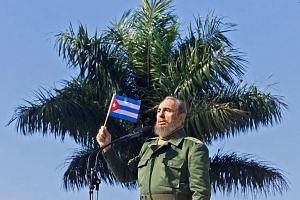 Former Cuban president Fidel Castro waving a flag during a visit Jan 27, 2001, to the Havana neighbourhood of San Jose de las Lajas.