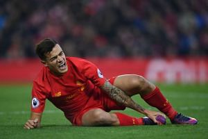 Liverpool's Brazilian midfielder Philippe Coutinho holds his foot as he lies on the pitch injured.
