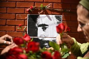 People place flowers next to a portrait of Cuban historic revolutionary leader Fidel Castro outside the Cuban embassy in Guatemala City on Nov 26, 2016.