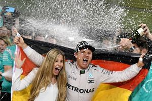 Staff members of Mercedes AMG Petronas F1 Team spray German driver Nico Rosberg and his wife Vivian Sibold with champagne as they celebrate at the end of the Abu Dhabi Formula One Grand Prix at the Yas Marina circuit on Nov 27, 2016.