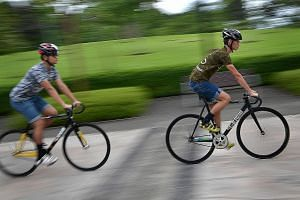 Students Sim Jia Fu (at right) and Jason A. Dennis have been gearing up for their first HolyCrit race by cycling almost every week from Woodlands to Marina Bay.
