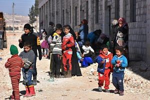 Displaced Syrian families gather at a makeshift camp after fleeing the eastern part of Aleppo.