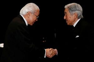 Singapore's President Tony Tan Keng Yam (left) shakes hands with Japan's Emperor Akihito upon his arrival for a state dinner at the Imperial Palace in Tokyo on Nov 30, 2016.