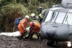 A rescue worker at the site of wreckage. Before it crashed, the BAe 146 aircraft radioed that it was having electrical problems, and that weather conditions were poor, but there was still no official word on the cause. A Colombian air force helicopte