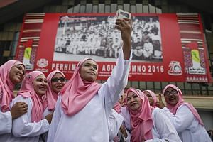 Party delegates taking a photo at the Umno general assembly in Kuala Lumpur yesterday. Mr Najib said yesterday that 10 bumiputera and Islamic bodies would be dismantled or weakened if the opposition takes power. But experts say most of these are form