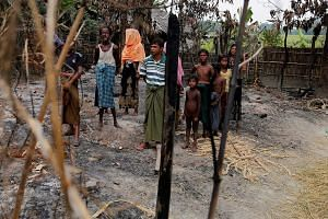 A Rohingya family viewing the remains of a market, which was set on fire, in their village, outside Maungdaw in Rakhine state, on Oct 27. The Rohingya issue is fast developing into a security threat with an adverse impact on peace in the region. Thei