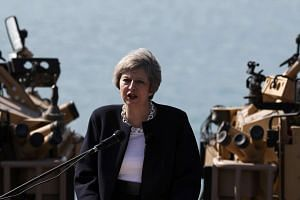 Britain's Prime Minister Theresa May addresses sailors on the deck of HMS Ocean in Manama, Bahrain on Dec 6, 2016.