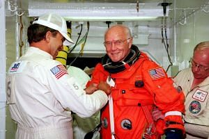 US astronaut and Senator John Glenn getting a hand from white room technicians moments before boarding the US space shuttle Discovery.