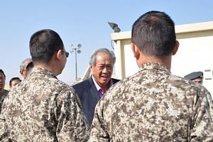 Defence Minister Ng Eng Hen with members of the SAF's Imagery Analysis Team that has been supporting the counter-ISIS coalition at the Combined Joint Task Force Headquarters in Kuwait.
