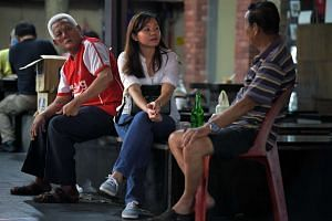Jayce Tham, 28, a volunteer chats with a resident in Chinatown.
