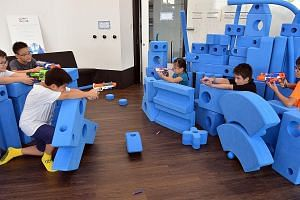 Kids enjoy a Nerf gun shootout at indoor playground Kaboodle Kids, which aims to stimulate creativity in kids and engage their senses, among other things.