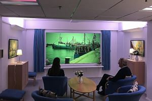 A room for dementia patients at Lindehaven Care Centre in Copenhagen, which uses different lighting to regulate the body's natural circadian rhythm. Images relevant to a patient's past, such as a familiar place, are also shown on a screen as a form o
