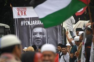 Indonesian protesters chant in front of a poster of Basuki Tjahaja Purnama as they march down the capital city's main street after a demonstration at Jakarta's National Monument Park on Dec 2, 2016.