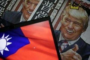 A newspaper headline with the illustration of US President-elect Donald Trump is pictured next to the flag of Taiwan in Taipei, Taiwan, on Dec 12, 2016.
