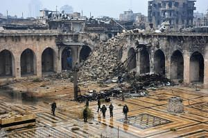 A general view shows Syrian pro-government forces walking in the ancient Umayyad mosque in the old city of Aleppo on Dec 13, 2016, after they captured the area.