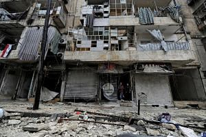 Boys stand amid the damage in the government-held al-Shaar neighbourhood of Aleppo, Syria, on Dec 13, 2016.