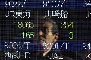 A pedestrian is reflected in a stock market indicator board in Tokyo, Japan on Dec 5, 2016.