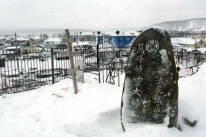 A Russian Orthodox cross next to a Japanese gravestone at a cemetery outside Kurilsk town on the island of Iturup.