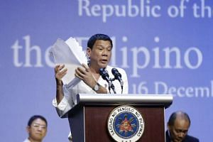 Philippine President Duterte holding a stack of documents on the drug industry in the Philippines at the Singapore Expo on Dec 16, 2016.