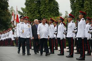 Mr Duterte with PM Lee at the Istana yesterday. Mr Lee said on Facebook that they discussed issues such as terrorism, the South China Sea and the US role in the region. Mr Duterte, accompanied by President Tan, inspecting the guard of honour at the I