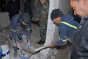 Workers remove the debris inside a police station in the Midan neighbourhood of Damascus where a young girl of about nine years of age blew herself up.